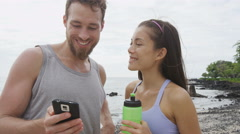 Friends looking at phone app after running workout - man and woman on smartphone - stock footage
