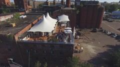 Quadrocopter shoot summer restaurant with white tents on roof of brick building Stock Footage