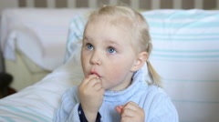 Cute little blue-eyed blonde girl watching cartoons and eating seeds and nuts Stock Footage