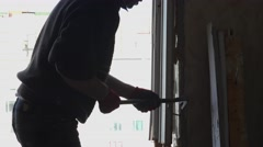 Construction worker dismantles and removes the old window. 4K. Stock Footage