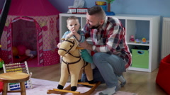 Dad with his son in a playroom , playing on the rocking horse  - stock footage