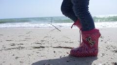 Kid girl legs in jeans walking on sandy sea shore strewn with seashells Stock Footage
