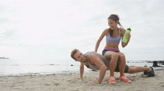 Fitness couple laughing having fun together on beach during workout Stock Footage