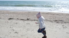 Little kid girl running on sandy sea shore in slow motion - family weekend Stock Footage