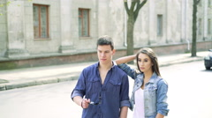 Young couple posing sideways on the street. 4k - stock footage
