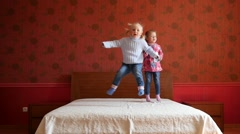 Two little cute child girls happily jumping on a big parental bed slow motion Stock Footage
