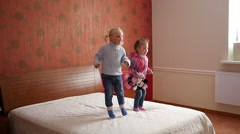 Two little cute child girls happily jumping on a big parental bed Stock Footage