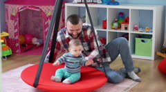 Dad play with son in playroom on the swing kids, and swinging kid on it  Stock Footage