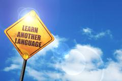 Yellow road sign with a blue sky and white clouds: learn another - stock illustration