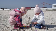 Two little kid girls playing with a sand on a sea shore Stock Footage
