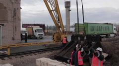Loading operations with rail crane and few workers in the dock Stock Footage
