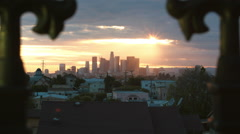 Dolly shot past wrought iron fence to Los Angeles Skyline at sunset Stock Footage