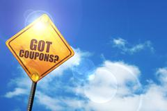 Yellow road sign with a blue sky and white clouds: got coupons? - stock illustration