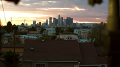 Dolly shot past wrought iron fence to Los Angeles Skyline at sunset - stock footage