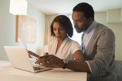 Couple paying bills on laptop Kuvituskuvat