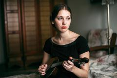 Caucasian woman playing ukulele in bedroom Kuvituskuvat