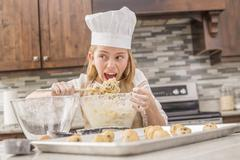 Caucasian girl tasting cookie dough in kitchen Stock Photos