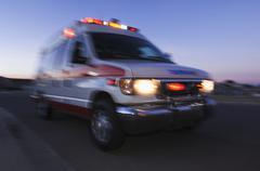 Blurred view of ambulance driving at dusk Kuvituskuvat