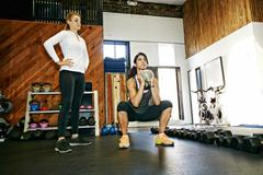 Woman working out with trainer in gymnasium Stock Photos