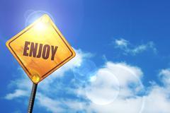 Stock Illustration of Yellow road sign with a blue sky and white clouds: enjoy