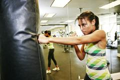 Mixed race woman hitting punching bag in gymnasium Stock Photos