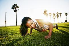Mixed race athlete doing push-ups in park Stock Photos