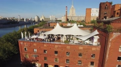 Quadrocopter fly above summer restaurant with white tents on roof of old Stock Footage
