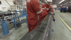 Two workers in red suits tighten the pipe Stock Footage