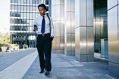 Black businessman using cell phone outside office building Stock Photos