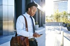Black businessman using cell phone outside office building - stock photo