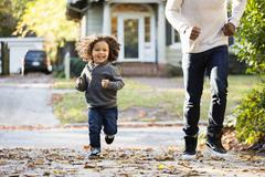 Father and son playing in driveway Stock Photos