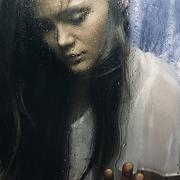 Caucasian woman standing at wet glass Stock Photos