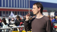 Young man smoking electronic cigarette outdoors in public place Stock Footage