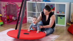 Happy mother play with her adorable baby boy in babyroom  Stock Footage