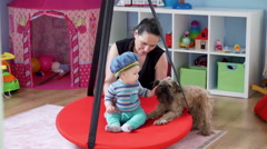 Mother play with baby and stroking the dog in babyroom on swing       Stock Footage
