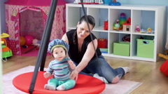 Mother swing her cute child on swinging in babyroom Stock Footage