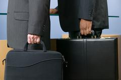Two businessmen holding briefcases - stock photo
