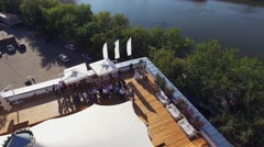 Quadrocopter fly over restaurant with white tent on roof of old building at Stock Footage