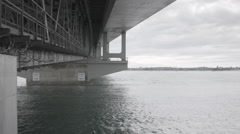 Underneath Auckland Harbour Bridge with tourists on guided tour end Stock Footage