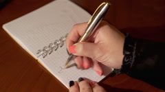 Woman's hand writes on the notebook word I LOVE YOU - stock footage