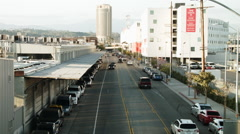 Cars and pedestrians travel in front of a row of warehouses Stock Footage