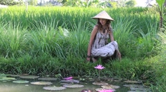 Girl in nature near the lake with lilies and paddy field in Bali, Indonesia Stock Footage