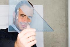 Man holding a set square Stock Photos