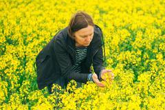 Agronomist woman examining oilseed rape flower blooming - stock photo