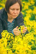 Female agronomist in field of blooming rapeseed - stock photo
