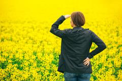 Agronomist standing in field of blooming cultivated rapese Stock Photos