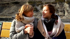 Mother and daughter sitting on a bench outdoors, talking, chatting, smiling Stock Footage