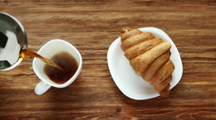 Pouring coffee and fresh croissant on wooden table - stock footage