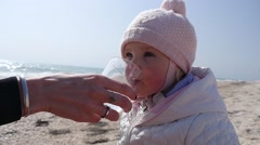 Mother gives child daughter drink clean pure water from glass on sea shore - stock footage