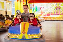 Father and his two sons, having a ride in the bumper car - stock photo